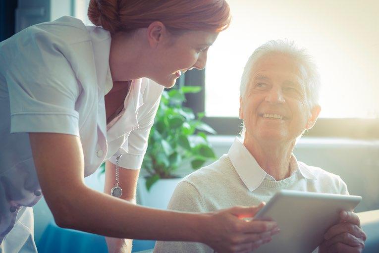 carer and mature man holding ipad