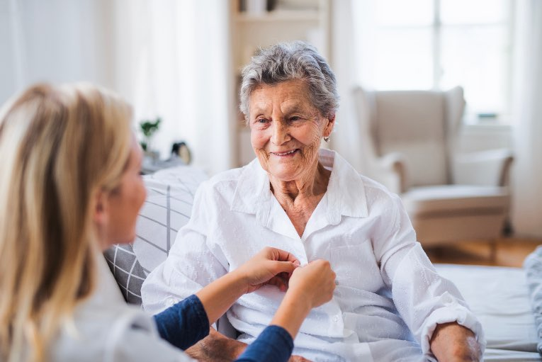 carer helping elderly woman do up her buttons