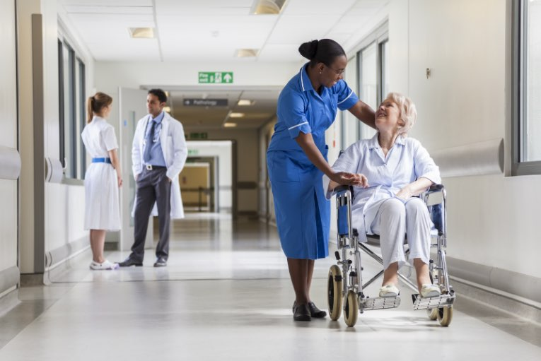 nhs nurse helping elderly woman in wheelchair